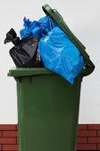 Lata de lixo verde sobre um fundo branco com um plástico — Foto Stock