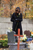Grieving woman at cemetery in autumn — Stock Photo