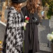 Women in mourning at cemetery in autumn — Stock Photo