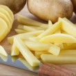 Cutting potatoes into chips — Stock Photo