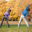 Couple exercising in park in fall — Stock Photo