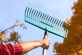 Man holding a rake — Stock Photo