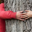 Couple surrounding tree trunk — Stock Photo