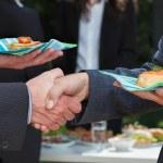 Business handshake during lunch — Stock Photo