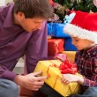 Father and son sitting under the christmas tree — Stock Photo
