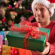 Man in santa's disguise with a present — Stock Photo