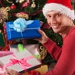Man with santa's hat leaving the gifts — Stock Photo