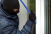 Housebreaker openning the window — Stock Photo
