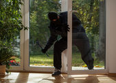 Burglar entering through the balcony window — Stock Photo