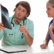 Doctor showing x-ray photo to his patient. — Stock Photo