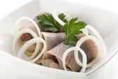 Herrings with sliced onion in white bowl — Stock Photo