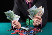 Man in casino wins heap of money — Stock Photo