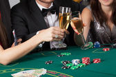 Friends in casino raising a glasses — Stock Photo