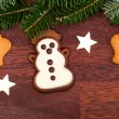 Gingerbread snowman and spruce twig — Stock Photo