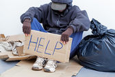 Homeless person sitting on the ground — Stockfoto