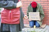 Woman passing poor man — Stock Photo