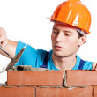 Construction mason installing red brick — Stock Photo