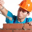 Constructor with putty knife building wall — Stock Photo