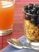 Cornflakes, blueberries and juice — Stock Photo