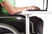 Disabled man sitting at a desk — Stock Photo