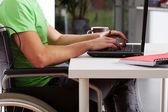 Disabled man writing on laptop — Stock Photo