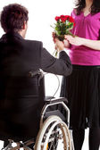 Man on wheelchair giving a flowers — Stock Photo