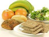 Crispbread, crunchy rolls, salad and fresh fruits — Stock Photo