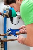 Handsome handyman turning off valves — Stock Photo