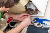 Handyman with tools repairing an equipment — Stock Photo