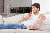 Bored man lying on couch — Stock Photo