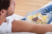 Man on couch with bowl full food — Stock Photo