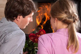 Couple roses fireplace — Stock Photo