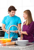 Young man helping his wife in household — Stock Photo