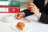 Croissant essen, bei der arbeit — Stockfoto