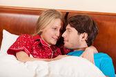 Happy couple lying in bed — Foto de Stock