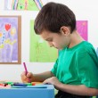 Stock Photo: Little boy drawing on the art lesson