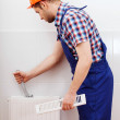 Professional plumber repairing white radiator — Stock Photo #40642859