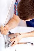 Professional plumber repairing a tap — Stock Photo