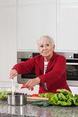 Elder lady cooking — Stock Photo
