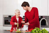 Son and mother making salad — Stock Photo