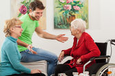 Young man tallking with two older women — Stock Photo