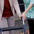 Stock Photo: Carer teaching using walker