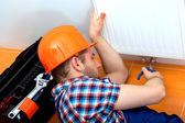 Handy man repairing heater — Stock Photo