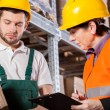 Worker consulting with manager in warehouse — Stock Photo