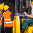 Worker operating forklift in warehouse — Stock Photo #41588643