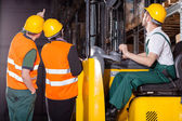 Worker operating forklift in warehouse — Stock Photo