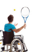 Man in wheelchair playing tennis — Stock Photo