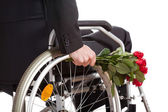Wheelchair and roses closeup — Stock Photo