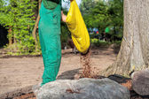 Gardener spills mulch on barrier — Stock Photo