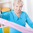 Elderly woman during folding laundry — Stock Photo